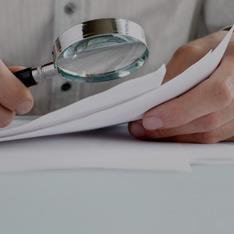 Pessoa analisando um documento com uma lupa