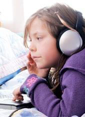 Criança com fones de ouvido em frente a um computador